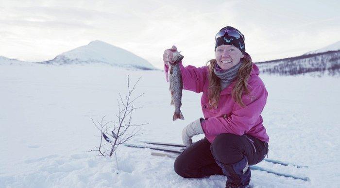 Happy woman Ice fishing in Lierne, Trøndelag.